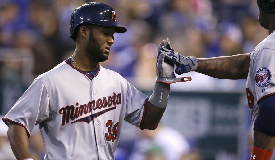 Minnesota Twins' Danny Santana (39) is congratulated by teammate Kennys Vargas after scoring on a single by Joe Mauer during the fourth inning of a baseball game at Kauffman Stadium in Kansas City, Mo., Tuesday, April 21, 2015. (AP Photo/Orlin Wagner)
