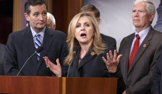 Rep. Marsha Blackburn, R-Tenn., center, flanked by Sen. Ted Cruz, R-Texas, left, and Rep. Mo Brooks, R-Ala., right, joins in criticizing President Barack Obama on immigration, Tuesday, Sept. 9, 2014, during a Republican news conference about the immigration crisis along the U.S.-Mexico border, Capitol Hill in Washington.  (AP Photo/J. Scott Applewhite)