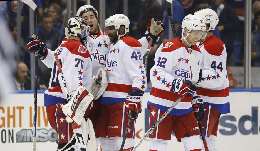 Washington Capitals right wing Tom Wilson (43) celebrates wiih Capitals goalie Braden Holtby (70), left, and right wing Joel Ward (42) after the Capitals defeated the New York Islanders in overtime of Game 4 of a first-round NHL Stanley Cup hockey playoff series at Nassau Coliseum in Uniondale, N.Y., Tuesday, April 21, 2015.  The Capitals evened their series at  2-2 on Nicklas Backstrom's tie-breaking goal. Washington Capitals center Evgeny Kuznetsov (92) of Russia skates away from the group. (AP Photo/Kathy Willens)