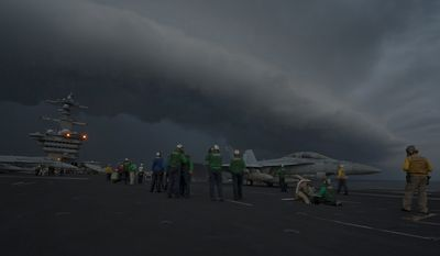 ARABIAN SEA (Jan. 21, 2012) Sailors prepare an F/A-18F Super Hornet assigned to Strike Fighter Squadron (VFA) 22 for launch on the flight deck as the Nimitz-class aircraft carrier USS Carl Vinson (CVN 70) passes through a storm front. U.S. Navy photo.