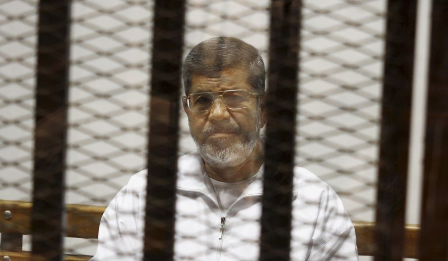 In this May 8, 2014, file photo, Egypt's ousted Islamist President Mohammed Morsi sits in a defendant cage in the Police Academy courthouse in Cairo, Egypt. (AP Photo/Tarek el-Gabbas, File)
