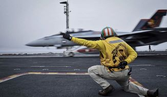 In this Wednesday, April 15, 2015 image released by the U.S. Navy, a shooter launches an F/A-18F Super Hornet, assigned to the Red Rippers of Strike Fighter Attack Squadron 11, off the flight deck aboard Nimitz-class aircraft carrier USS Theodore Roosevelt in the Fifth Fleet area of operations. he U.S. Navy has dispatched USS Theodore Roosevelt toward the waters off Yemen to join other American ships prepared to intercept any Iranian vessels carrying weapons to Houthi rebels, U.S. officials said on Monday. (Mass Communication Specialist Seaman Anna Van Nuys/U.S. Navy Media Content Services via AP)