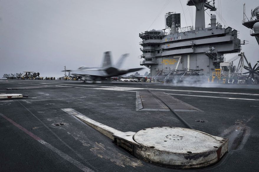In this Wednesday, April 15, 2015 image released by U.S. Navy Media Content Services, an F/A-18E Super Hornet, assigned to the Knighthawks of Strike Fighter Attack Squadron 136, lands on the flight deck aboard Nimitz-class aircraft carrier USS Theodore Roosevelt in the Fifth Fleet area of operations. he U.S. Navy has dispatched USS Theodore Roosevelt toward the waters off Yemen to join other American ships prepared to intercept any Iranian vessels carrying weapons to Houthi rebels, U.S. officials said on Monday.  (Mass Communication Specialist Seaman Anna Van Nuys/U.S. Navy Media Content Services via AP)