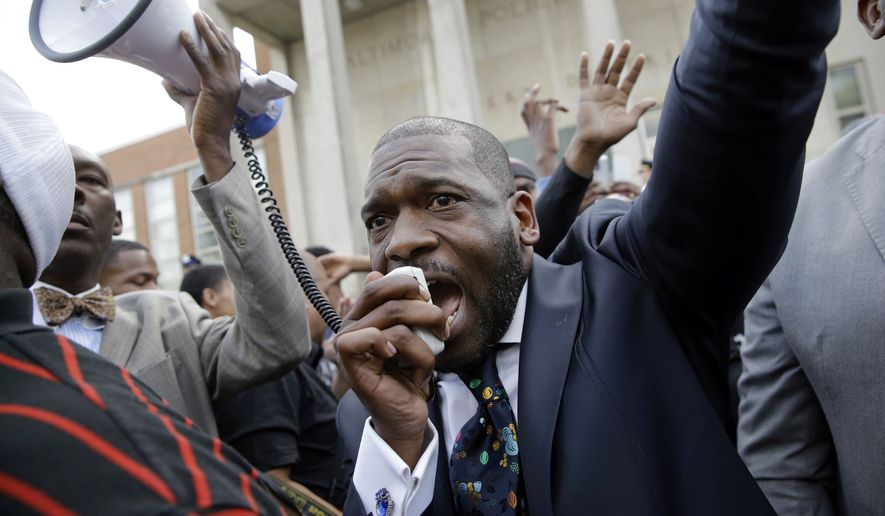 Rev. Jamal Bryant leads a rally outside of the Baltimore Police Department's Western District station during a march and vigil for Freddie Gray on Tuesday in Baltimore. Mr. Gray died from spinal injuries a week after he was arrested and transported in a police van. (Associated Press)