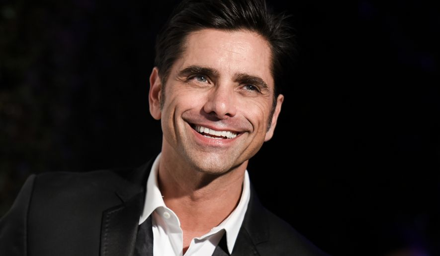 """FILE - In this Feb. 22, 2015 file photo, John Stamos arrives at the 87th Academy Awards - 2015 Elton John AIDS Foundation Oscar Party in West Hollywood, Calif.  Stamos says he's on board for a 13-episode reboot of the sitcom """"Full House"""" for Netflix and that he hopes as many members of the original cast as possible will return. Stamos told Jimmy Kimmel on Monday, April 20, that the first episode will be a reunion and it will turn into a spinoff with Candace Cameron, who played the oldest daughter in the show, now having the """"full house"""" with three sons. He said he and the producers had been trying for awhile to find the best way of reviving the sitcom, which originally appeared on ABC from 1987 to 1995. (Photo by Richard Shotwell/Invision/AP, File)"""