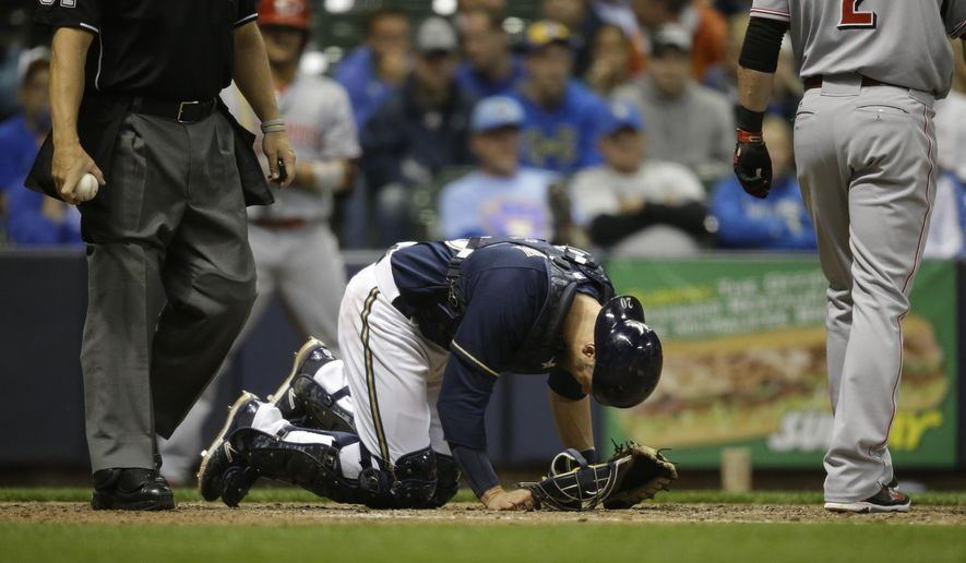 Milwaukee Brewers catcher Jonathan Lucroy bends over after taking a foul tip off his toe during the sixth inning of a baseball game  against the Cincinnati Reds Monday, April 20, 2015, in Milwaukee. Lucroy left the game and the Brewers announced after the game that Lucroy will be placed on the DL with a broken left toe. (AP Photo/Jeffrey Phelps)