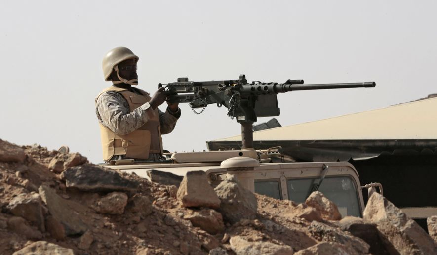 A Saudi soldier sits on top of an armor vehicle as he aims his weapons, on the border with Yemen, at a military point in Najran, Saudi Arabia, Tuesday, April 21, 2015. (AP Photo/Hasan Jamali)