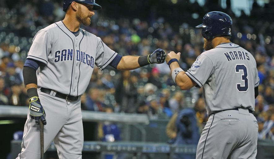San Diego Padres' Will Middlebrooks, left congratulates Derek Norris after Norris scores a run against the Colorado Rockies during the first inning of a baseball game Monday, April 20, 2015, in Denver. (AP Photo/Jack Dempsey)
