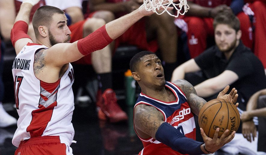 Washington Wizards guard Bradley Beal (3) drives past Toronto Raptors center Jonas Valanciunas (17) during the first half in Game 2 in the first round of the NBA basketball playoffs, Tuesday, April 21, 2015,  in Toronto. (Nathan Denette/The Canadian Press via AP)  MANDATORY CREDIT