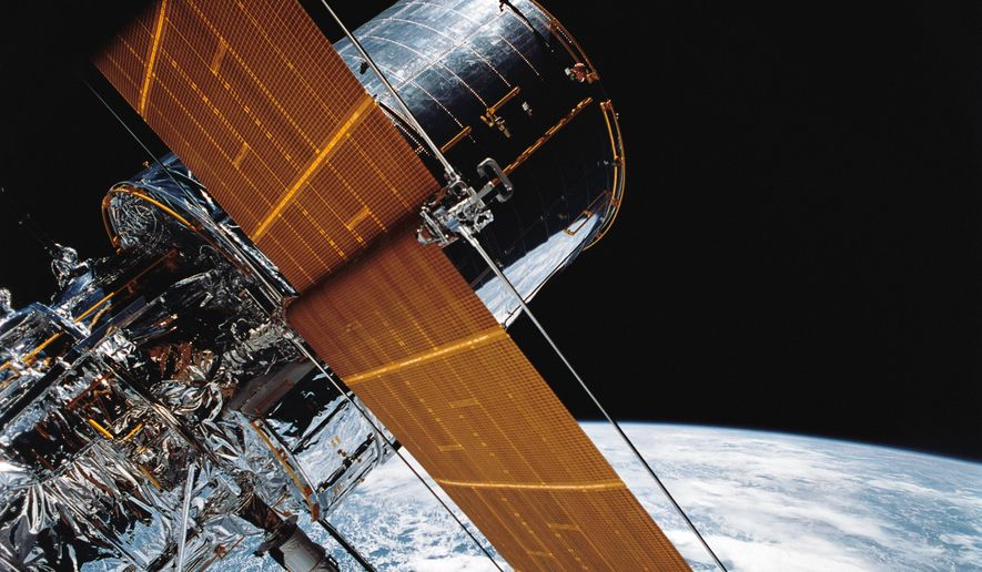 In this April 25, 1990, photograph provided by NASA, most of the giant Hubble Space Telescope can be seen as it is suspended in space by Discovery's Remote Manipulator System (RMS) following the deployment of part of its solar panels and antennae. (NASA via AP)