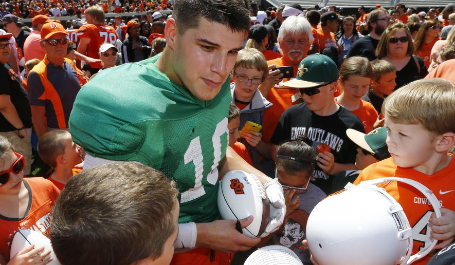 Oklahoma State quarterback Mason Rudolph signs autographs for young fans following the Oklahoma State NCAA college spring football game Stillwater, Okla, Saturday, April 18, 2015. (AP Photo/Sue Ogrocki)