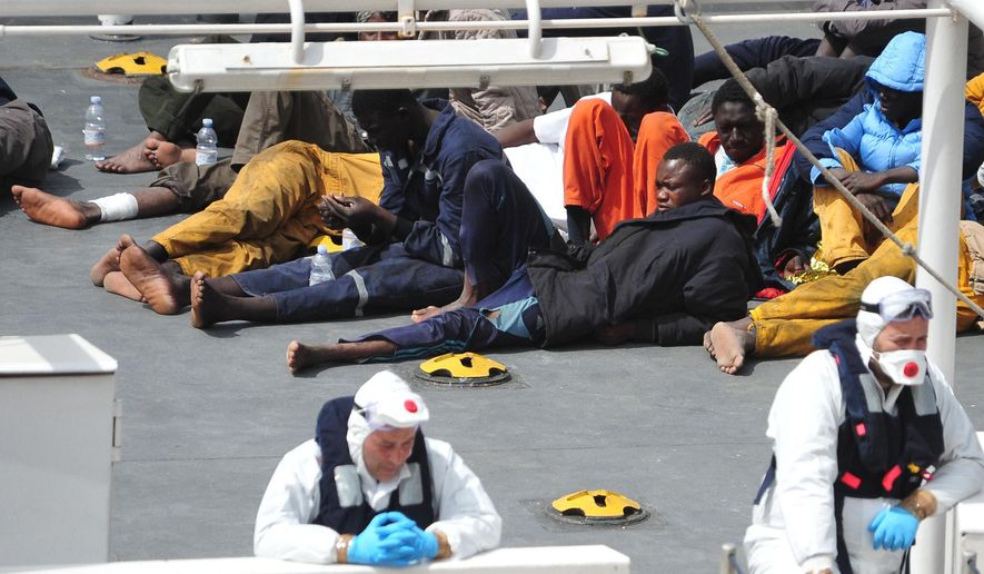 In this Monday, April 20, 2015, file photo, survivors of the smuggler's boat that overturned off the coast of Libya rest on the deck of the Italian Coast Guard ship Bruno Gregoretti, in Valletta's Grand Harbour. The United Nations refugee agency said Tuesday that more than 800 people were believed to have drowned in the weekend sinking of a boat packed with migrants trying to reach Europe, making it the deadliest such disaster in the Mediterranean. (AP Photo/Lino Azzopardi, File)