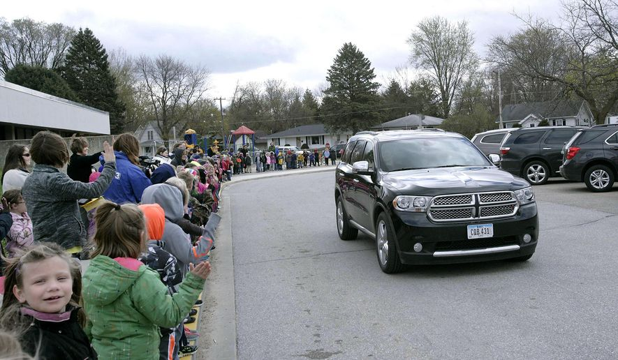 In this photo taken on Tuesday, April 21, 2015, students and teachers from Washington Elementary School in Charles City, Iowa line the sidewalk in front of the school to wave to Amy Heiter as she is brought to the school to receive her teaching certificate. Heiter, who student taught at the school, has terminal cancer. (Jeff Heinz/Globe-Gazette via AP)