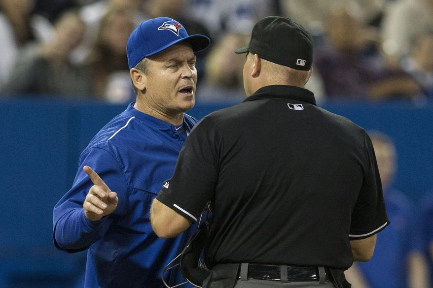 Toronto Blue Jays manager John Gibbons, left, argues with home plate umpire Mark Carlson after a ball from Baltimore Orioles pitcher Jason Garcia narrowly missed Toronto batter Jose Bautista during the seventh inning of a baseball game Tuesday, April 21, 2015, in Toronto. (Chris Young/The Canadian Press via AP)