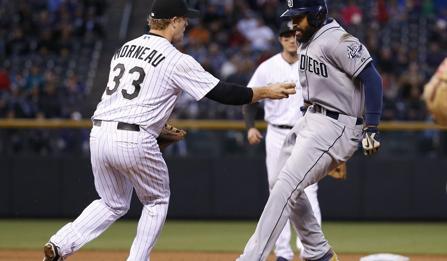 Colorado Rockies first baseman Justin Morneau runs down San Diego Padres' Matt Kemp between first and second base during the third inning of a baseball game, Tuesday, April 21, 2015, in Denver. (AP Photo/Jack Dempsey)