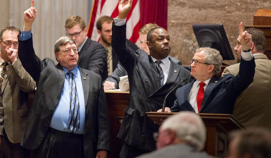 Supporters of a bill to extend in-state tuition to non-citizens who are lawfully present in the United States signal their position on a motion from the well of the House chamber on Wednesday, April 22, 2015 in Nashville, Tenn.. From right are Reps. Mark White, R-Memphis; Joe Towns, D-Memphis, and Harry Brooks, R-Knoxville.  (AP Photo/Erik Schelzig.)