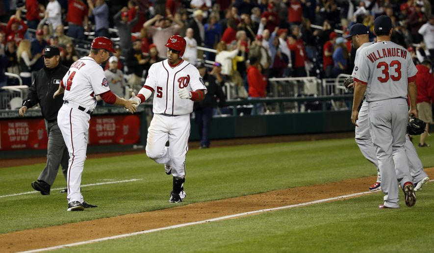 Washington Nationals' Yunel Escobar (5) gets congratulations from third base coach Bob Henley (14), for his game winning solo home run as St. Louis Cardinals relief pitcher Carlos Villanueva (33) walks off the field in the 10th inning of a baseball game at Nationals Park, Tuesday, April 21, 2015, in Washington. The Nationals won 2-1, in 10 innings. (AP Photo/Alex Brandon)