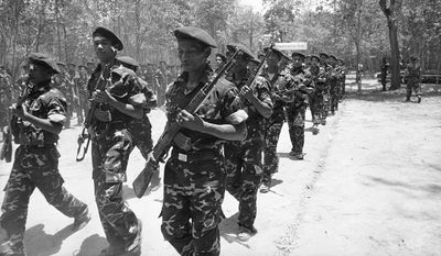 Cambodian coalition soldiers carrying their Chinese-made AK-47s march at the welcoming ceremony of President Prince Norodom Sihanouk as he visits in Simanouk Buri, Cambodia, in 1983. (Associated PRess)