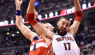 The Wizards' Marcin Gortat battles Toronto's Jonas Valanciunas for a rebound Tuesday in Game 2. Washington holds a big rebounding edge in the first-round series. (Frank Gunn/The Canadian Press via Associated Press)