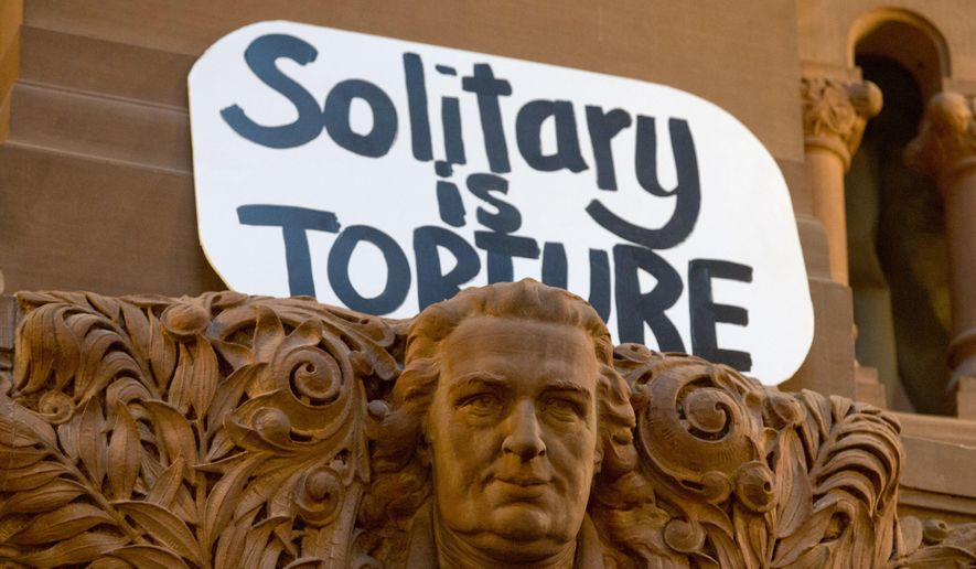 A sign rests on a sandstone carving on the Great Western Staircase before a rally against solitary confinement Wednesday, April 22, 2015, in Albany, N.Y. (AP Photo/Mike Groll) ** FILE **