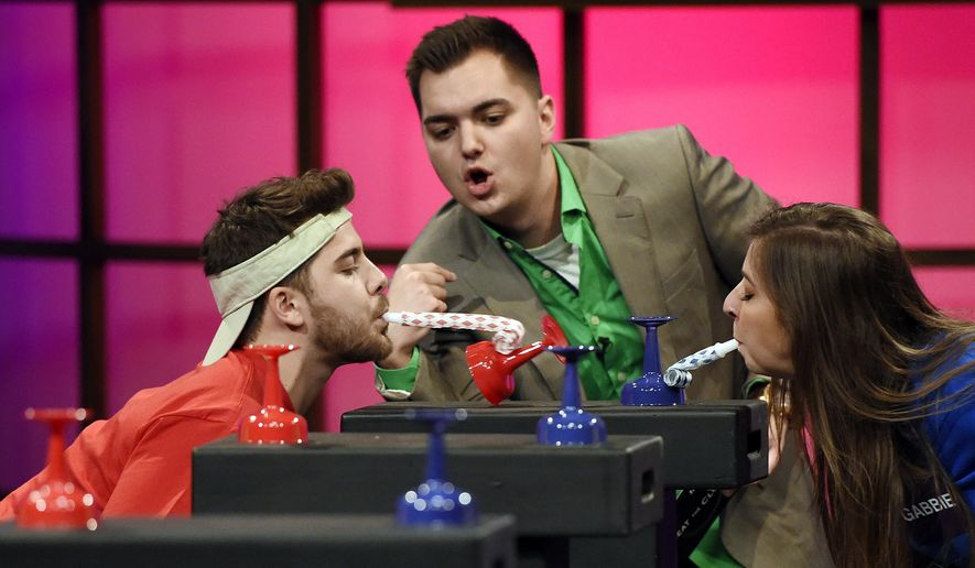 """In this Tuesday, March 31, 2015 photo, host Elliot Morgan, center, watches over contestants Dominic DeAngelis, left, and Gabie Hanna as they try to knock over glasses with party whistles during a taping of the classic game show """"Beat the Clock,"""" at YouTube Space LA, in Los Angeles. FremantleMedia, the company that owns the rights to """"Beat the Clock"""" and more than 150 other game show formats, commissioned original digital content studio Tiny Riot! to produce content for Buzzr.  (Photo by Chris Pizzello/Invision/AP)"""