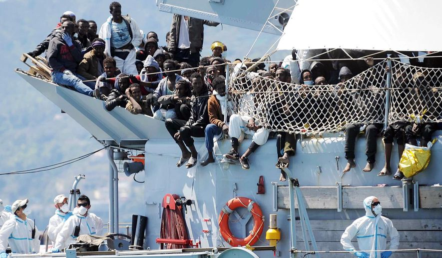 Migrants wait to disembark from the Italian Navy vessel 'Chimera' in the harbor of Salerno, Italy, Wednesday, April 22, 2015. Italy pressed the European Union on Wednesday to devise concrete, robust steps to stop the deadly tide of migrants on smugglers' boats in the Mediterranean, including setting up refugee camps in countries bordering Libya. Italian Defense Minister Roberta Pinotti also said human traffickers must be targeted with military intervention. (AP Photo/Francesco Pecoraro) ** FILE **