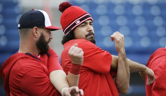 Washington Nationals' Anthony Rendon, right, stretches during a spring training baseball workout, Wednesday, Feb. 25, 2015, in Viera, Fla. (AP Photo/David Goldman)