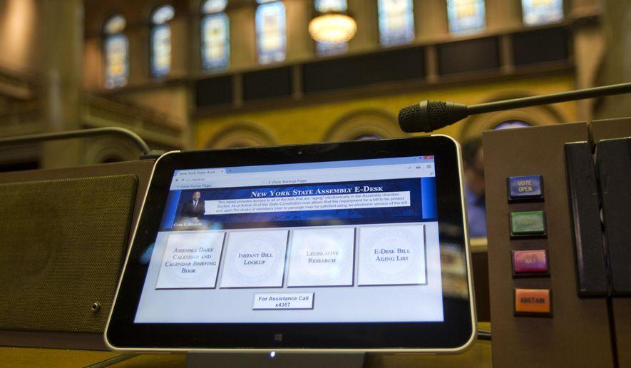 An electronic tablet sits on a legislator's desk in the Assembly Chamber at the Capitol on Wednesday, April 22, 2015, in Albany, N.Y. The 150 desks in the ornate chamber of the Assembly now have computer tablets mounted, with four large boxes on the screens that legislators can click to see their calendars, look up bills, research legislation and find out where a particular measure stands in the aging process before it can be voted on. (AP Photo/Mike Groll)