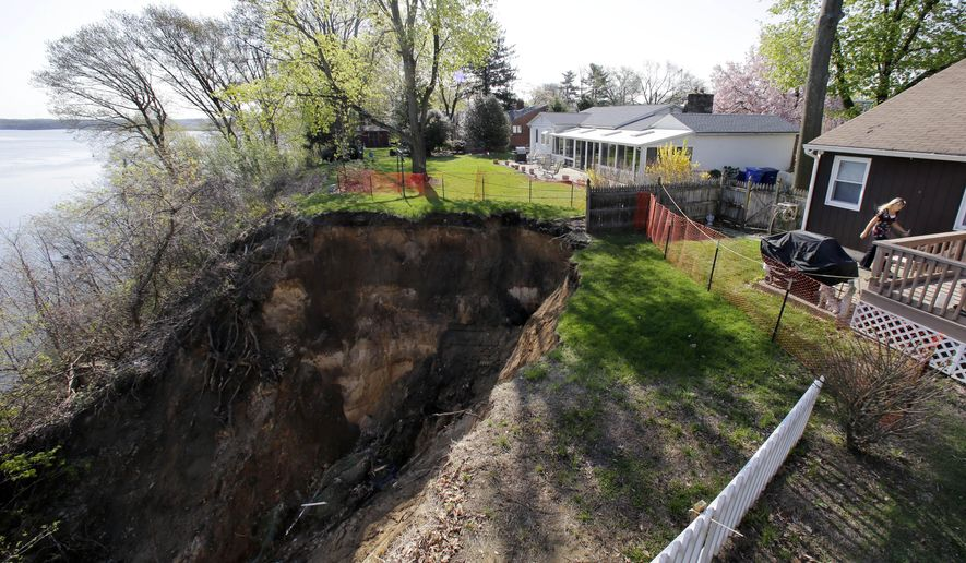 Lynne O'Dell walks past large landslide from her E. Front Street home, back right, to her neighbors' home Wednesday, April 22, 2015, in Florence, N.J. Engineers are going to evaluate the landslide that has left the two New Jersey homes on the brink of falling into the Delaware River. Erosion has been a problem for several years to homes on East Front Street in Florence. But the recent rain has created a hole that is growing larger. (AP Photo/Mel Evans)