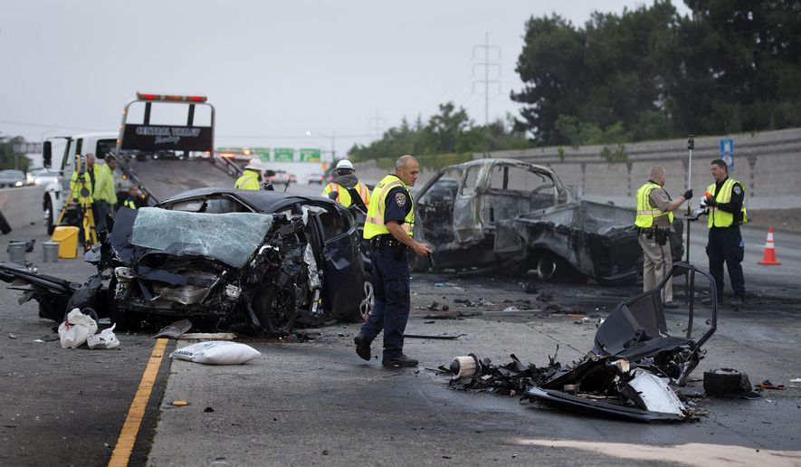 Officials investigate the accident on U.S. Route 50 where authorities say four people were killed in a wrong-way crash that blocked several lanes of a freeway early Wednesday, April 22, 2015, in Sacramento, Calif. The collision resulted in the death of the wrong-way driver, a woman in the Toyota Prius, shown here, and three men in a Ford pickup. A third vehicle was involved, but the driver suffered only minor injuries.  (Randy Pench/The Sacramento Bee via AP)  MAGS OUT; LOCAL TELEVISION OUT MANDATORY CREDIT