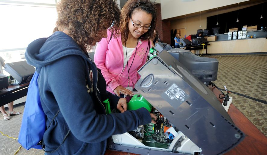 "In a May 23, 2012 photo, Whitmore Lake students Joanna Liverance, 16, and Jasmine Munir, 16, work together as they assemble a PC during a break out session of Digital Divas, Cyber Security in the 21st Century, at the Eastern Michigan Student Center in Ypsilanti, Mich. Eastern Michigan University is again hosting a gathering of more than 500 girls and young women from middle and high schools around the state for the ""Digital Divas"" conference on Friday, April 24, 2015. (AP Photo/The Ann Arbor News, Melanie Maxwell)"