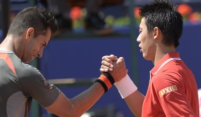 Kei Nishikori of Japan, right, shakes hands with Santiago Giraldo of Colombia, at the end of the Barcelona open tennis tournament in Barcelona, Spain, Thursday, April 23, 2015. (AP Photo/Manu Fernandez)