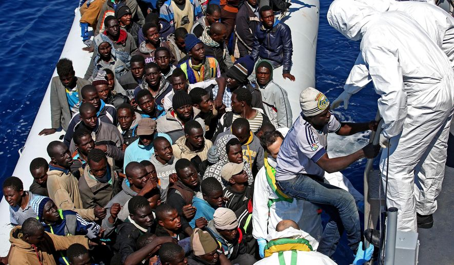 """In this photo made available Thursday, April 23, 2015, migrants crowd and inflatable dinghy as rescue vassel """"Denaro"""" of the Italian Coast Guard approaches them, off the Libyan coast, in the Mediterranean Sea, Wednesday, April 22, 2015. European Union leaders gathering for an extraordinary summit are facing calls from all sides to take emergency action to save lives in the Mediterranean, where hundreds of migrants are missing and feared drowned in recent days. (Alessandro Di Meo/ANSA via AP Photo)"""