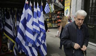 An man walk past a kiosk with Greek flags for sale in central Athens, Thursday, April 23, 2015. Greece is running perilously short of cash amid an impasse in bailout talks with its international creditors. Eurozone finance ministers are to meet in Riga, Latvia, on Friday but hopes of a deal on Greece there have diminished. (AP Photo/Petros Giannakouris)