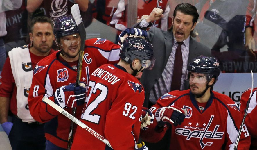 Washington Capitals left wing Alex Ovechkin (8), from Russia, celebrates with center Evgeny Kuznetsov (92), from Russia, left wing Marcus Johansson (90), from Sweden, and assistant coach Lane Lambert, right, after Kuznetsov's goal during the third period of Game 5 in the first round of the NHL hockey Stanley Cup playoffs against the New York Islanders, Thursday, April 23, 2015, in Washington. The Capitals won 5-1. (AP Photo/Alex Brandon)