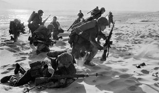 Newly-landed U.S. Marines make their way through the sands of Red Beach at Da Nang, Vietnam on their way to reinforce the air base as South Vietnamese Rangers battled guerrillas about three miles south of the beach. (AP Photo/Peter Arnett, File)