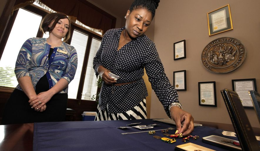 Lauren Brewer, property controller with the Arkansas Auditor of State's office, left, watches as Angela Allen of Memphis examines her father's military medals at the Arkansas state Capitol in Little Rock, Ark., Friday, April 24, 2015. The medals and other unclaimed items in a deposit box were turned over to the state after being found in a Helena, Ark., bank. (AP Photo/Danny Johnston)