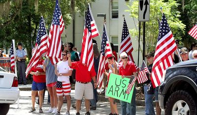 Flag supporters attend a rally Friday, April 24, 2015, in Valdosta, Ga. Uproar over a protest in which demonstrators walked on an American flag has prompted a south Georgia university to cancel classes ahead of the rally expected to draw crowds of flag supporters to Valdosta. (Jason Stewart/The Daily Times via AP)