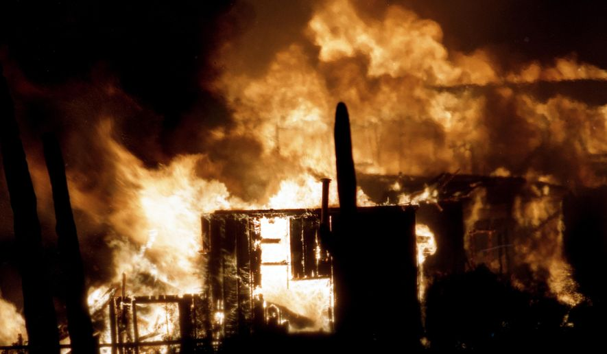 """In this photo taken on April 24, 1995, fire engulfs Old Tucson Movie Studios, in Tuscon, Ariz. The arson that lit up Old Tucson studios 20 years ago still blazes on in the minds of local firefighters. The Arizona Daily Star of Tucson reports that the fire that destroyed more than 40 percent of the historic movie set and theme park was a """"career fire"""" for many. (Linda Seeger Salazar/Arizona Daily Star via AP)  ALL LOCAL TELEVISION OUT; PAC-12 OUT; MANDATORY CREDIT; GREEN VALLEY NEWS OUT"""
