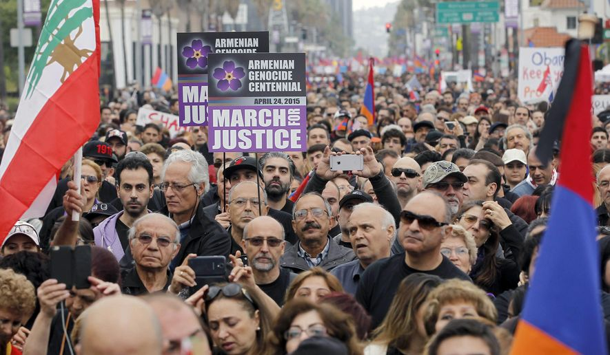Demonstrators carrying signs and Armenian flags march in Los Angeles Friday, April 24, 2015, to commemorate the 100th anniversary of the killings of an estimated 1.5 million Armenians during the Ottoman Empire rule over Turkey, and to press for recognition by Turkey and the U.S. that the killings should be considered genocide. (AP Photo/Nick Ut)