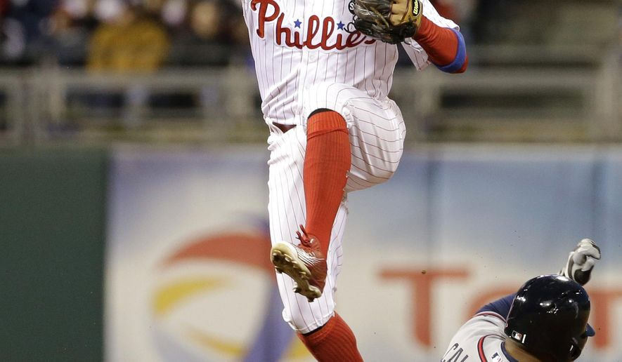 Philadelphia Phillies shortstop Freddy Galvis, left, makes a throw to first base after forcing out Atlanta Braves' Alberto Callaspo (1) at second on a double play hit into by Nick Markakis during the fourth inning of a baseball game, Friday, April 24, 2015, in Philadelphia. Markakis was out at first on the play. (AP Photo/Matt Slocum)