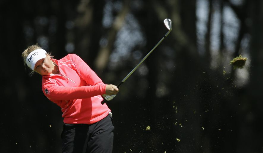 Brooke Henderson, of Canada, hits her approach shot from the fairway to the ninth green of the Lake Merced Golf Club during the second round of the Swinging Skirts LPGA Classic golf tournament Friday, April 24, 2015, in Daly City, Calif. (AP Photo/Eric Risberg)