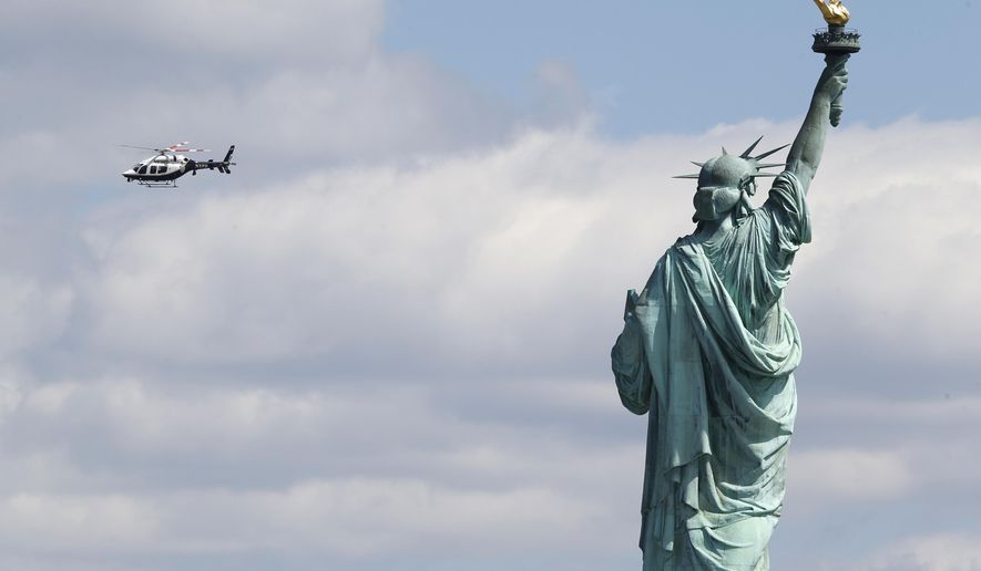 A New York Police helicopter circles over Liberty Island where the Statue of Liberty. (AP Photo/Julio Cortez)