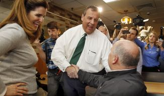 FILE - In this April 14, 2015 file photo, New Jersey Gov. Chris Christie, R-N.J. , accompanied by his wife Mary Pat, shakes hands with Don VanDenBerghe during a luncheon stop at Caesario's Pizza in downtown Manchester, N.H.  Christie's wife has left her lucrative job at a Wall Street firm as her husband prepares for a potential run for the White House. A spokesman for Christie's office confirmed Friday that Mary Pat Christie recently resigned as managing director at Angelo, Gordon and Co. and is putting her career on hiatus.  (AP Photo/Jim Cole, File)