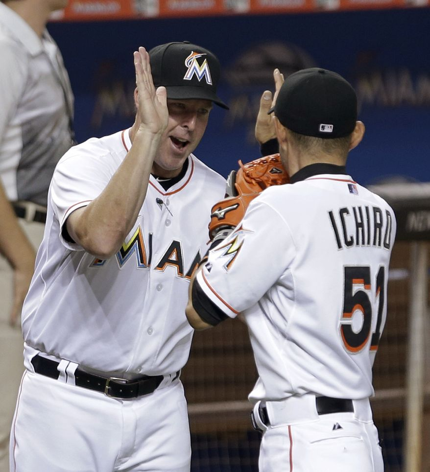 Miami Marlins manager Mike Redmond, left, gives a high-five to Ichiro Suzuki (51) after the team's 3-2 win against the Washington Nationals in a baseball game, Friday, April 24, 2015, in Miami. (AP Photo/Alan Diaz)