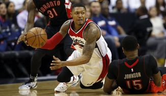 Washington Wizards guard Bradley Beal (3) passes the ball as he falls between Toronto Raptors forwards Terrence Ross (31) and Amir Johnson (15) during the first half of Game 3 in the first round of the NBA basketball playoffs Friday, April 24, 2015, in Washington. (AP Photo/Alex Brandon)