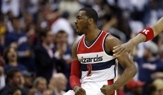 Washington Wizards guard John Wall (2) celebrates after a basket during the first half of Game 3 in the first round of the NBA basketball playoffs against the Toronto Raptors, Friday, April 24, 2015, in Washington. (AP Photo/Alex Brandon)