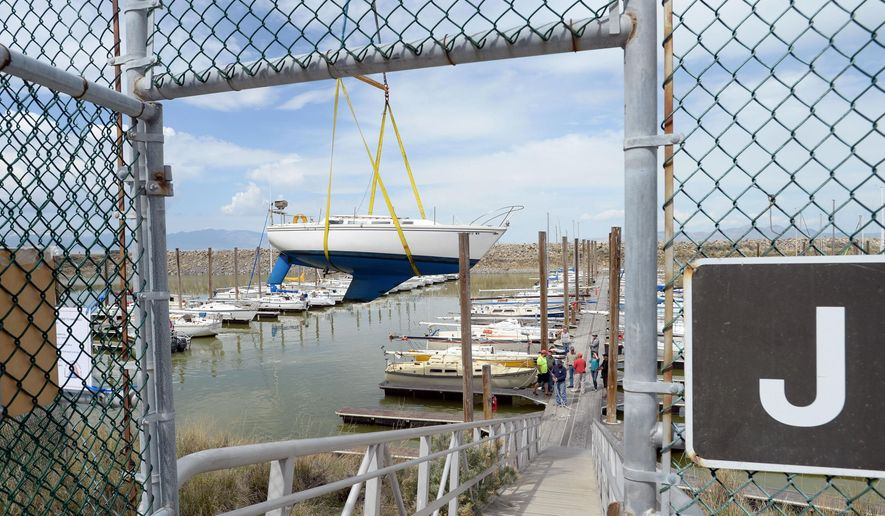 A crane lifts a sailboat from its slip at the Great Salt Lake State Marina in Tooele, Utah, Thursday, April 23, 2015. The two-day removal of 80 sailboats began Thursday in preparation for a sediment removal project later this year. The lake's waters are reaching historic lows and without dredging, boats risk damage from keels becoming wedged in the mud. (Steve Griffin/The Salt Lake Tribune via AP)
