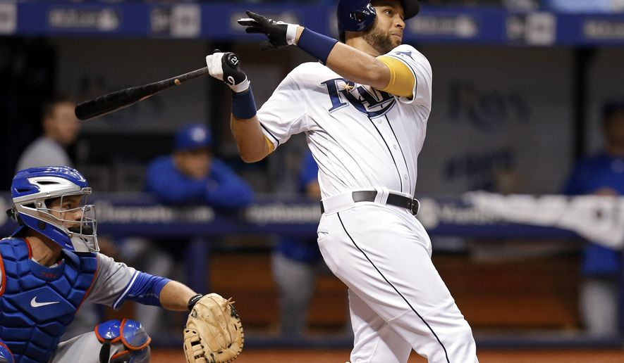Tampa Bay Rays' James Loney follows through on a two-run home run in front of Toronto Blue Jays catcher Josh Thole during the fourth inning of a baseball game Friday, April 24, 2015, in St. Petersburg, Fla. (AP Photo/Mike Carlson)
