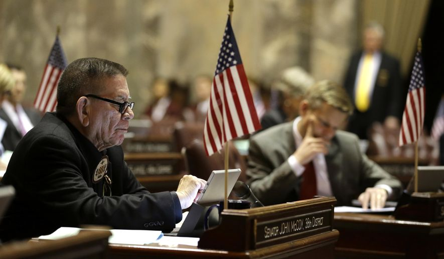 Sen. John McCoy, D-Tulalip, left, works at his desk during a session of the Washington state Legislature, Friday, April 24, 2015, at the Capitol in Olympia, Wash. Flags were displayed on Senators' desks Friday due to a resolution honoring Washington companies who have made special efforts to hire military veterans. McCoy is a 20-year veteran of the U.S. Air Force. The regular legislative session was expected to end later in the day, ahead of a special session that is scheduled to begin Wednesday, April 29, 2015. (AP Photo/Ted S. Warren)